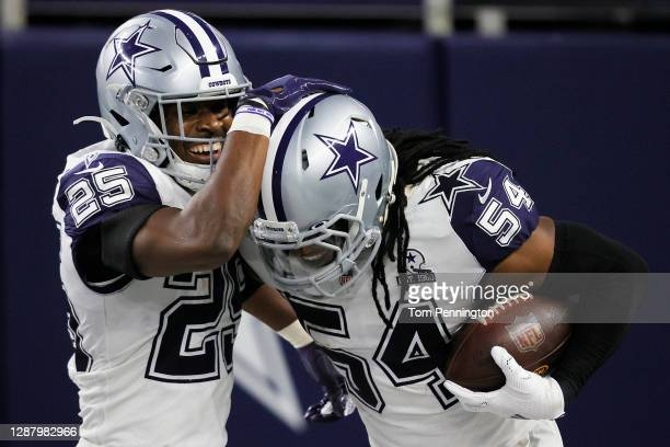 Jaylon Smith of the Dallas Cowboys celebrates his interception alongside Xavier Woods during the third quarter of a game against the Washington...
