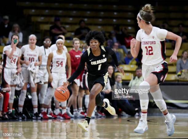 Jaylyn Sherrod of the Colorado Buffaloes dribbles down court in front of the Stanford Cardinal bench and Lexie Hull of the Stanford Cardinal during...