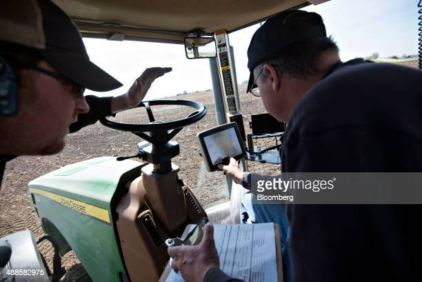 Jaymes Maciejewski left talks with farmer Kent Bickett as he loads seed variety codes into a computer on a Deere Co John Deere tractor pulling a...