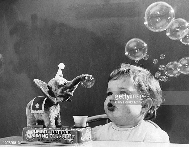Jayne Fincher and her new toy elephant, 1 December 1959. 'Meet the elephant who's for ever blowing bubbles, pretty bubbles in the air. They fly so...