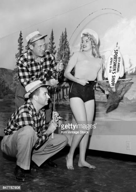 Jayne Mansfield poses with two fishermen for a publicity shoot for a California sportsman show