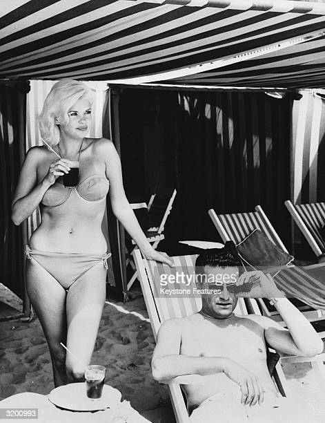 Jayne Mansfield relaxing at Lido Beach in Venice with film producer Enrico Bomba