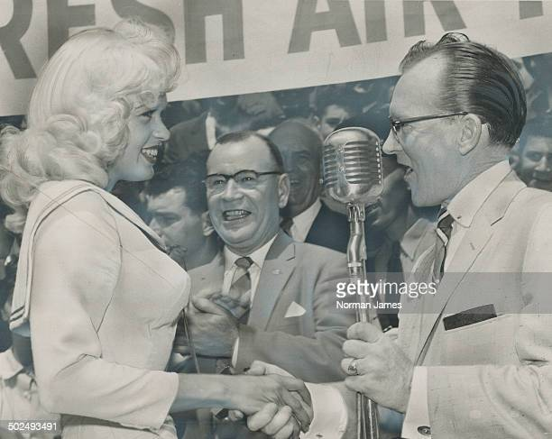 Jayne Mansfield shakes hands with TV singer Billy O'Connor at tumultuous city hall welcome for the curvaceous star Con Ford Brand applauds in the...