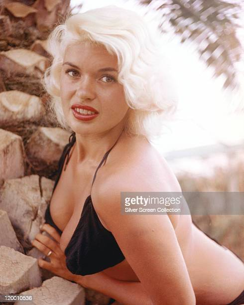 Jayne Mansfield US actress wearing a black bikini while posing beside some rocks circa 1955