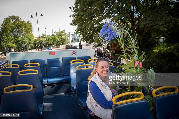 Jayne Squirrell from Canterbury rides on the top deck of an open top bus with flowers purchased on the final day of the Chelsea Flower Show at Royal...
