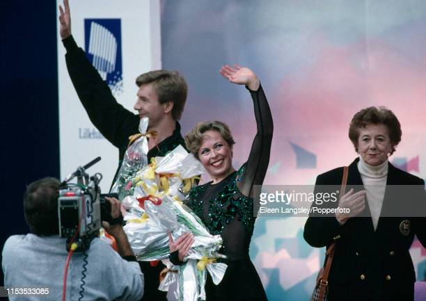 Jayne Torvill and Christopher Dean of Great Britain acknowledge the audience after receiving flowers for their original program in the Ice dancing...