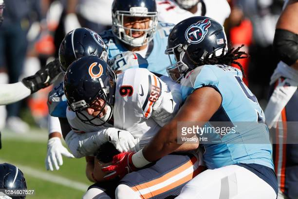 Jayon Brown and Larrell Murchison of the Tennessee Titans combine to tackle Nick Foles of the Chicago Bears during the second quarter at Nissan...