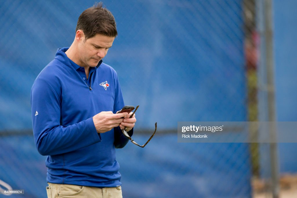 Jays GM Ross Atkins checks his phone while watching the pitchers work out. Toronto Blue Jays welcome the entire squad today as position players join the pitchers and catchers in Dunedin. Today was the first full workout as they team prepares for the upcoming Grapefruit season at Bobby Mattick Training Centre. Toronto Star/Rick Madonik