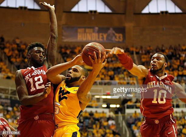 Jaysean Paige of the West Virginia Mountaineers battles through Khadeem Lattin and Jordan Woodard of the Oklahoma Sooners during the game at the WVU...