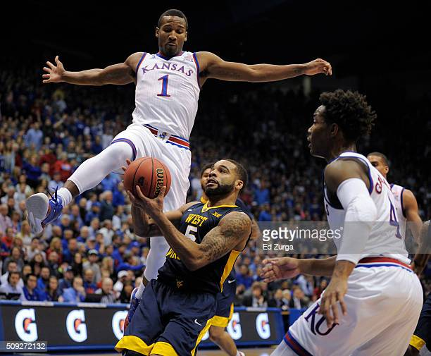 Jaysean Paige of the West Virginia Mountaineers drives to the basket against Wayne Selden Jr #1 and Devonte' Graham of the Kansas Jayhawks in the...