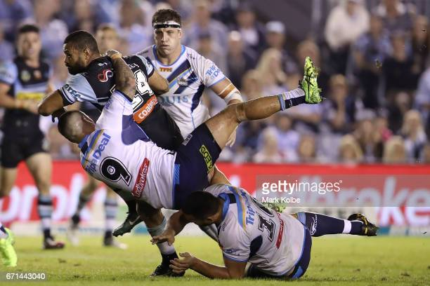 Jayson Bukuya of the Sharks is tackled by Nathan Peats Jarrod Wallace and Ryan James of the Titans during the round eight NRL match between the...