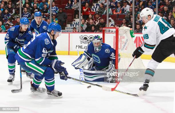 Jayson Megna Luca Sbisa and Nikita Tryamkin of the Vancouver Canucks look on as Tomas Hertl of the San Jose Sharks takes a shot on Ryan Miller of the...
