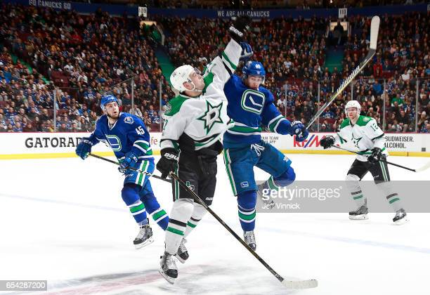 Jayson Megna of the Vancouver Canucks and Devin Shore of the Dallas Stars jump to reach a puck during their NHL game at Rogers Arena March 16 2017 in...
