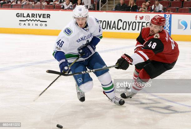 Jayson Megna of the Vancouver Canucks and Jordan Martinook of the Arizona Coyotes battle for a loose puck during the first period at Gila River Arena...