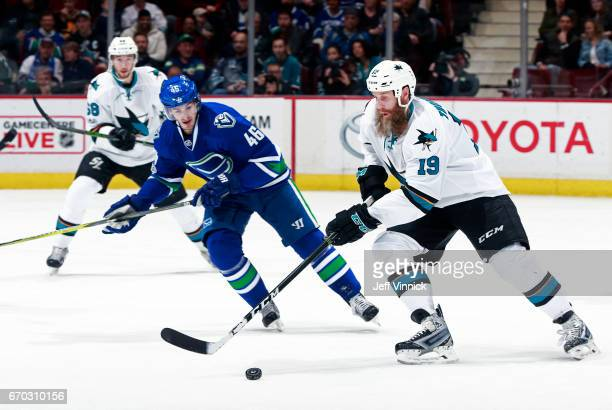 Jayson Megna of the Vancouver Canucks looks on as Joe Thornton of the San Jose Sharks skates up ice with the puck during their NHL game at Rogers...