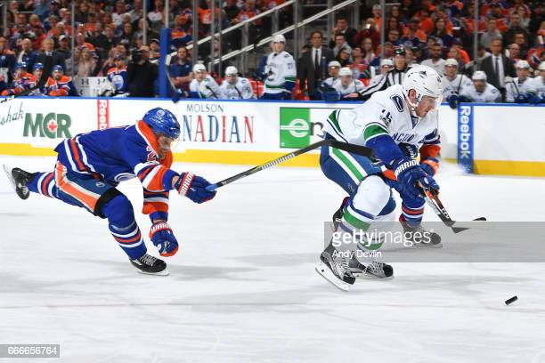 Jayson Megna of the Vancouver Canucks skates white the puck while being pursued by Andrej Sekera of the Edmonton Oilers on April 9 2017 at Rogers...