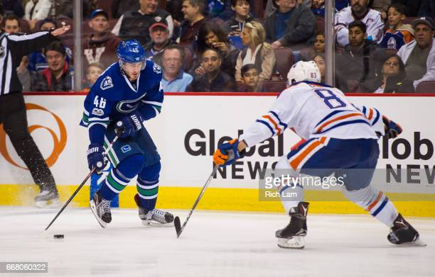 Jayson Megna of the Vancouver Canucks tries to get past Matthew Benning of the Edmonton Oilers in NHL action on April 8 2017 at Rogers Arena in...