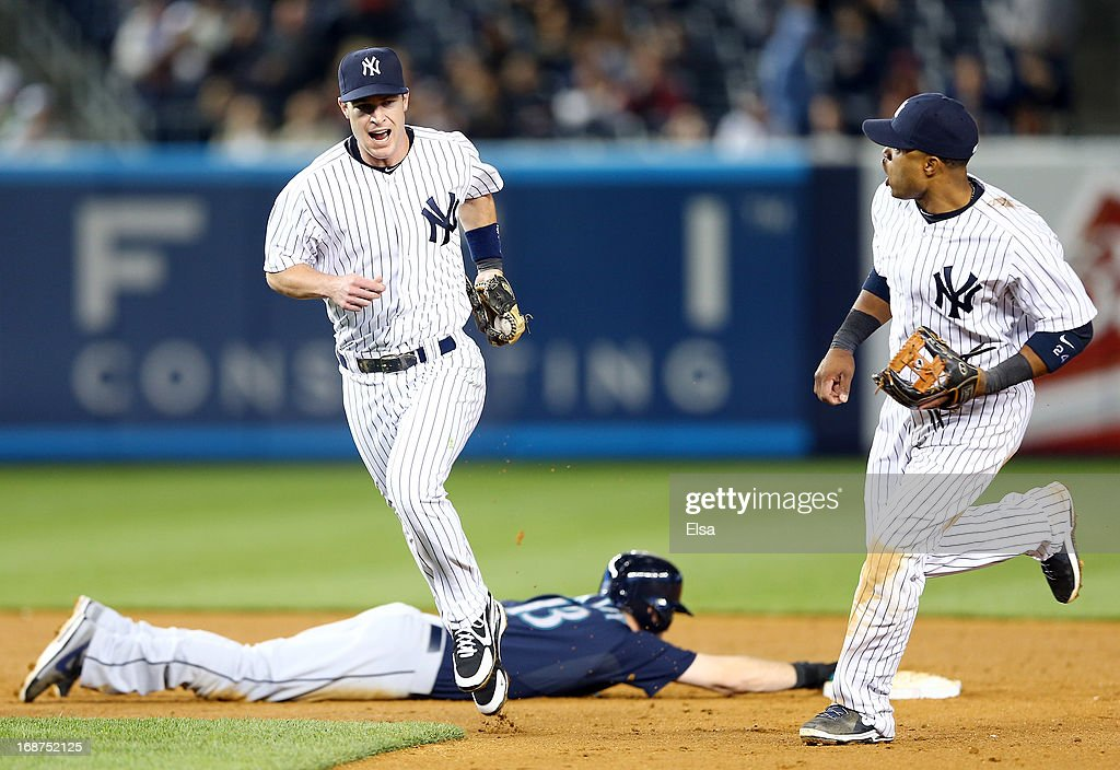 Jayson Nix #17 of the New York Yankees celebrates his inning ending out with teammate Robinson Cano #24 as Dustin Ackley #13 of the Seattle Mariners is out on May 14, 2013 at Yankee Stadium in the Bronx borough of New York City.The New York Yankees defeated the Seattle Mariners 4-3.
