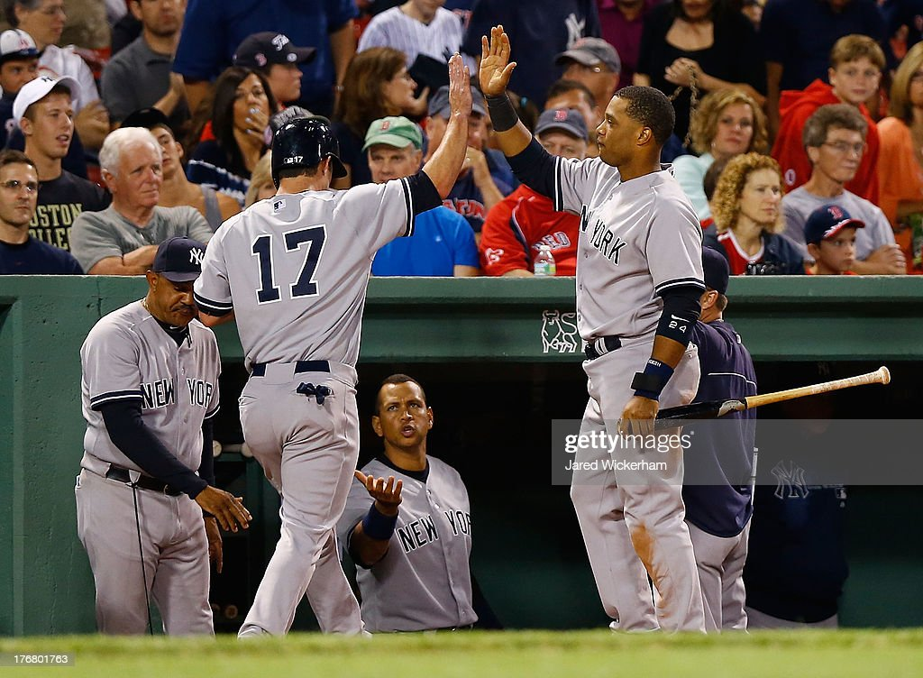 Jayson Nix #17 of the New York Yankees is congratulated by teammates in the dugout after scoring in the 9th inning against the Boston Red Sox during the game on August 19, 2013 at Fenway Park in Boston, Massachusetts.