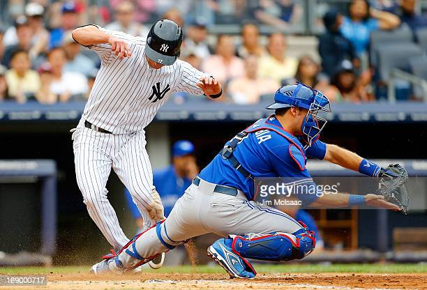 Jayson Nix of the New York Yankees scores a third inning run ahead of the tag attempt from JP Arencibia of the Toronto Blue Jays at Yankee Stadium on...