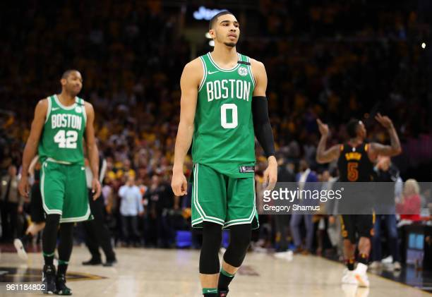 Jayson Tatum and Al Horford of the Boston Celtics walk off the court as JR Smith of the Cleveland Cavaliers reacts after the Cavaliers defeated the...