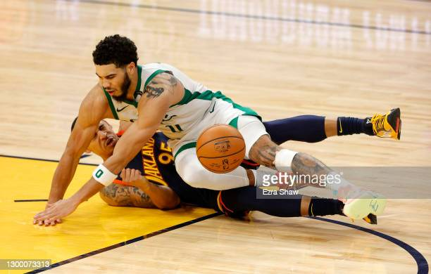 Jayson Tatum of the Boston Celtics and Juan Toscano-Anderson of the Golden State Warriors go for a loose ball at Chase Center on February 02, 2021 in...