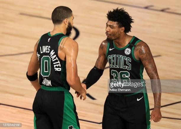 Jayson Tatum of the Boston Celtics and Marcus Smart of the Boston Celtics react to a shot during the fourth quarter against the Toronto Raptors in...