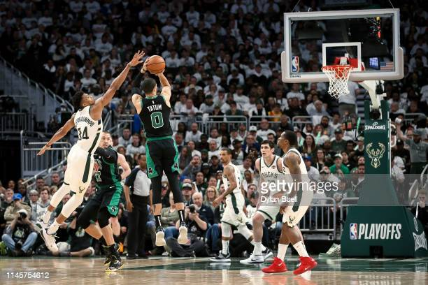 Jayson Tatum of the Boston Celtics attempts a shot while being guarded by Giannis Antetokounmpo of the Milwaukee Bucks in the third quarter during...