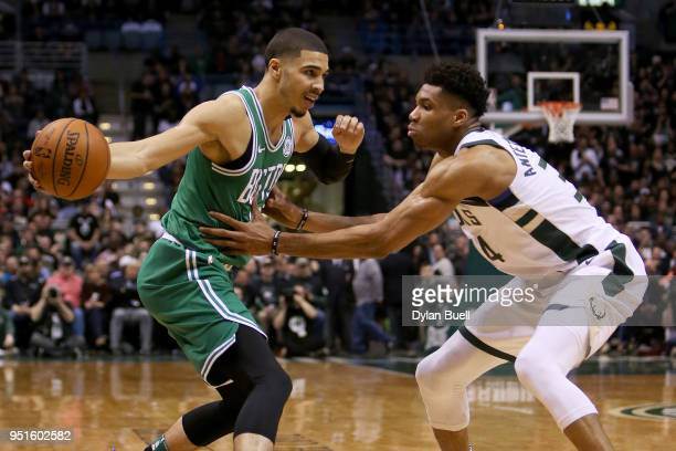 Jayson Tatum of the Boston Celtics dribbles the ball while being guarded by Giannis Antetokounmpo of the Milwaukee Bucks in the second quarter during...