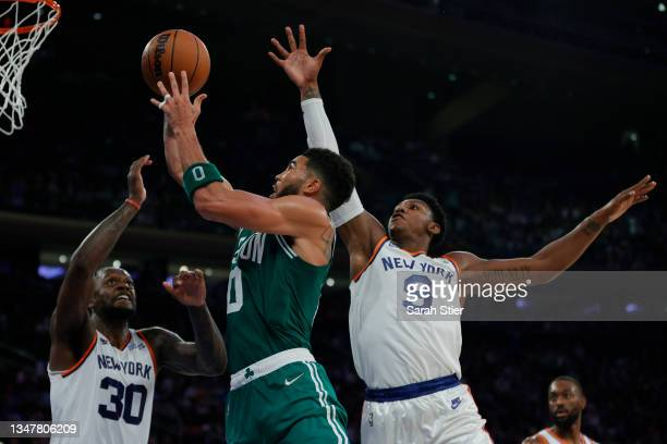 Jayson Tatum of the Boston Celtics goes to the basket as Julius Randle and RJ Barrett of the New York Knicks defend during the second half at Madison...