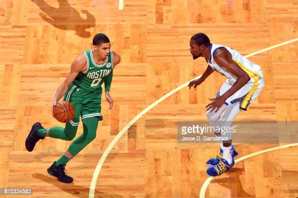 Jayson Tatum of the Boston Celtics handles the ball against Kevin Durant of the Golden State Warriors on November 16 2017 at the TD Garden in Boston...