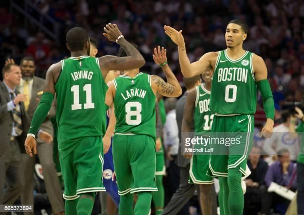 Jayson Tatum of the Boston Celtics high fives Kyrie Irving and Shane Larkin against the Philadelphia 76ers at the Wells Fargo Center on October 20...