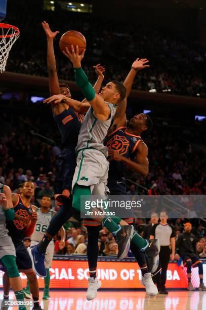 Jayson Tatum of the Boston Celtics in action against Frank Ntilikina and Damyean Dotson of the New York Knicks at Madison Square Garden on February...