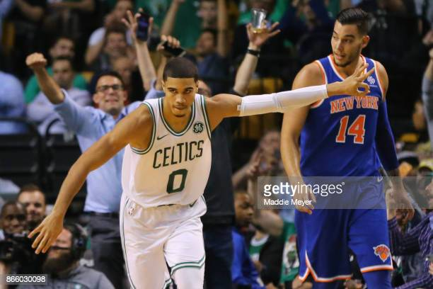 Jayson Tatum of the Boston Celtics reacts in front of Willy Hernangomez of the New York Knicks after hitting a three point shot during the fourth...