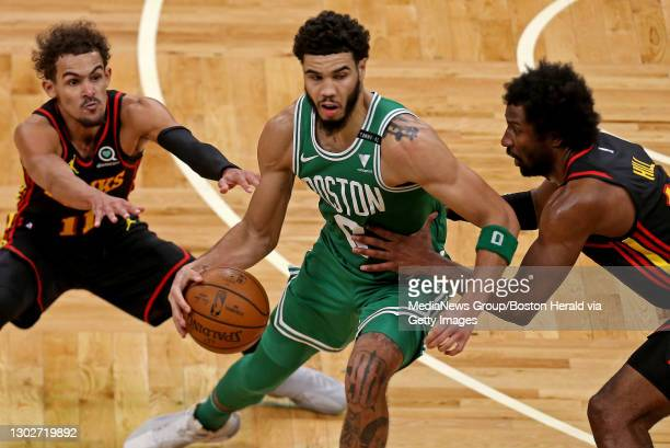 Jayson Tatum of the Boston Celtics tries to avoid Trae Young and Solomon Hill of the Atlanta Hawks during the fourth quarter of the NBA game at the...