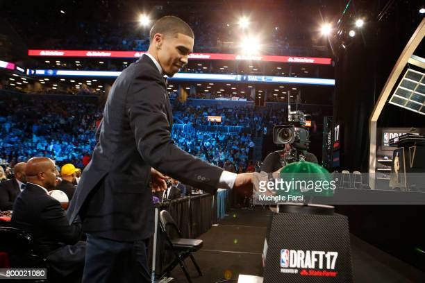 Jayson Tatum picks up his Boston Celtics cap after being selected third at the 2017 NBA Draft on June 22 2017 at Barclays Center in Brooklyn New York...