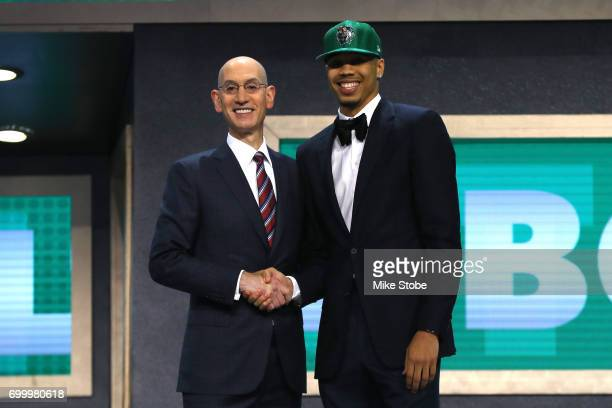 Jayson Tatum walks on stage with NBA commissioner Adam Silver after being drafted third overall by the Boston Celticsduring the first round of the...