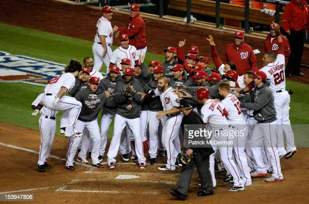 Jayson Werth of the Washington Nationals celebrates with his teammates as he jumps on home plate to score on his solo gamewinning walkoff home run in...