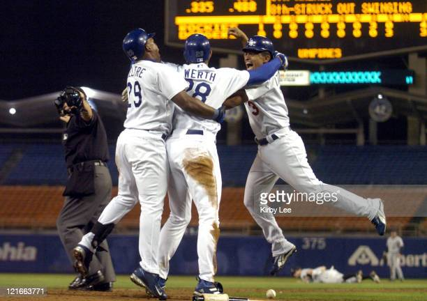 Jayson Werth of the Los Angeles Dodgers is embraced by Adrian Beltre and Cesar Izturis after scoring from third base with the winning run in the...