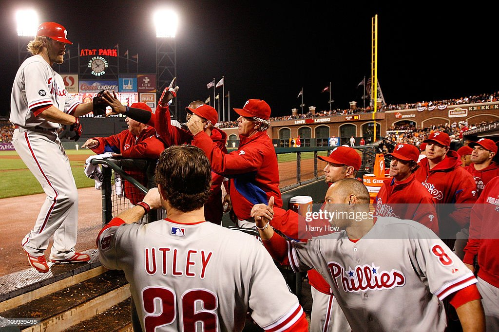 Jayson Werth #28 of the Philadelphia Phillies celebrates a solo home run in the dugout with his teammates while taking on the San Francisco Giants in the ninth inning of Game Five of the NLCS during the 2010 MLB Playoffs at AT&T Park on October 21, 2010 in San Francisco, California.