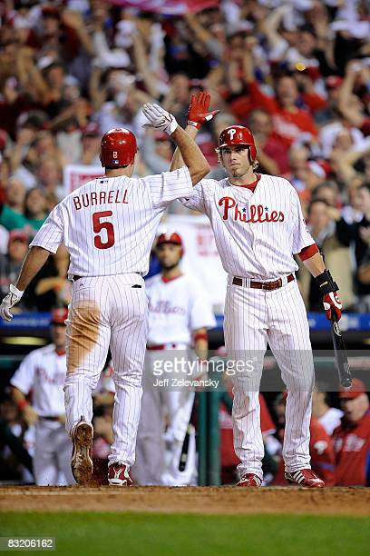Jayson Werth of the Philadelphia Phillies congratulates Pat Burrell after hitting a solo home run to give the Phillies a 3-2 lead in the bottom of...