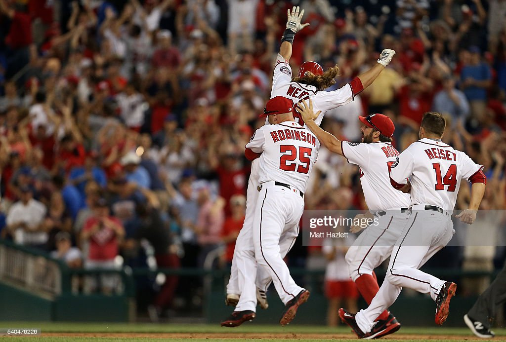 Jayson Werth #28 of the Washington Nationals celebrates with teammates Clint Robinson #25, Tanner Roark #57, and Chris Heisey #14 after hitting a walk-off single RBI in the twelfth inning to win 5-4 against the Chicago Cubs at Nationals Park on June 15, 2016 in Washington, DC.