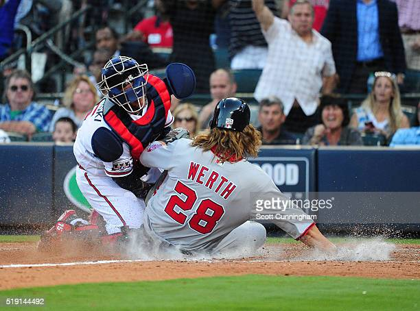 Jayson Werth of the Washington Nationals slides into home to score a ninth inning run against A J Pierzynski of the Atlanta Braves at Turner Field on...