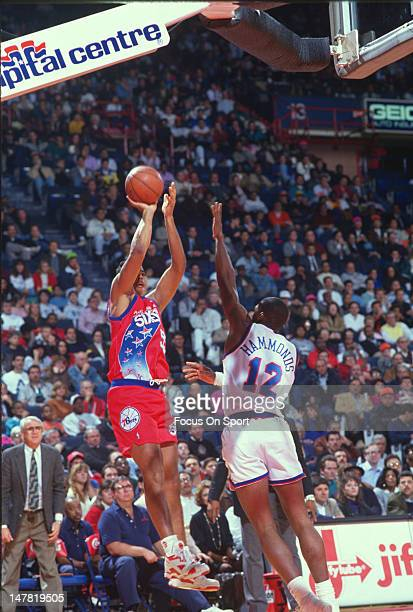 Jayson Williams of the Philadelphia 76ers shoots over Tom Hammonds of the Washington Bullets during an NBA basketball game circa 1991 at the Capital...
