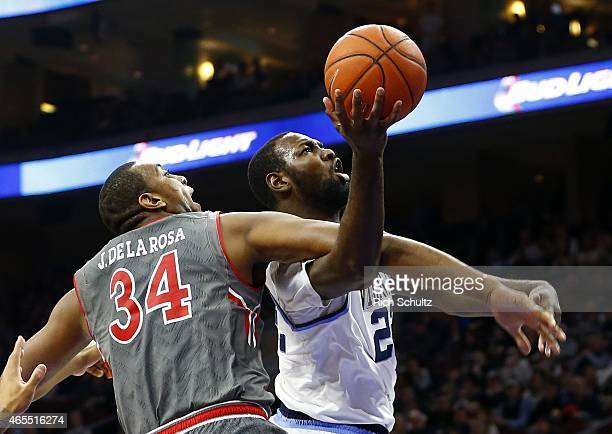 JayVaughn Pinkston of the Villanova Wildcats takes a shot as Joey De La Rosa of the St John's Red Storm defends during the first half of an NCAA...