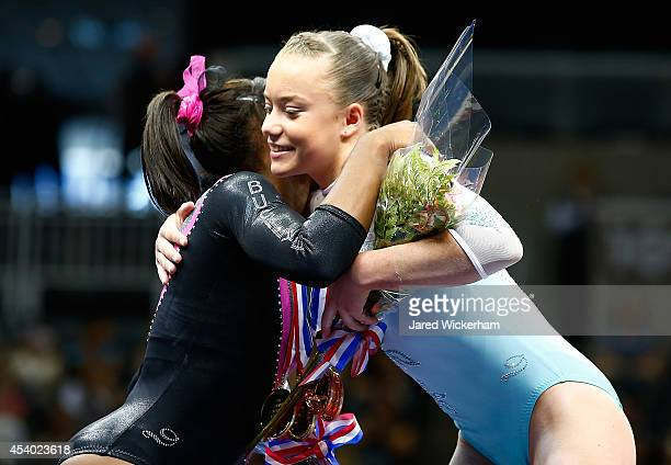 Jazmyn Foberg embraces Nia Dennis following their first and second places finishes in the junior women finals during the 2014 PG Gymnastics...