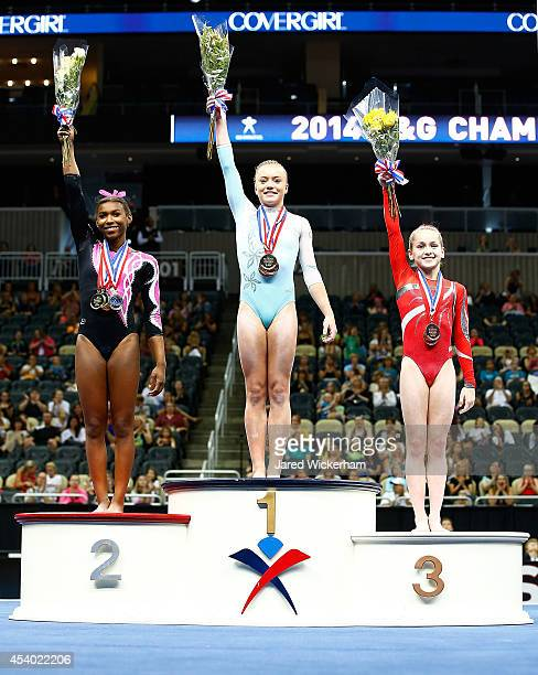 Jazmyn Foberg Nia Dennis and Norah Flatley stand on the winners podium following the junior women finals during the 2014 PG Gymnastics Championships...