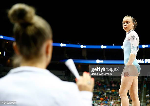 Jazmyn Foberg talks with her coach Maggie Haney before competing on the floor exercise in the junior women finals during the 2014 PG Gymnastics...