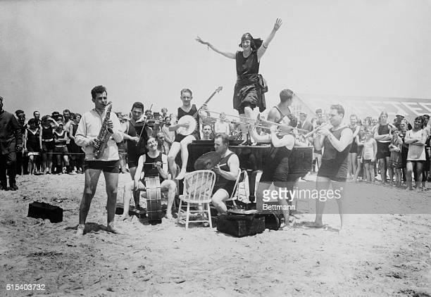 Jazz Band and Flapper Benny Krueger's band plays on the beach at Brighton Beach in Brooklyn as girl dances on the piano