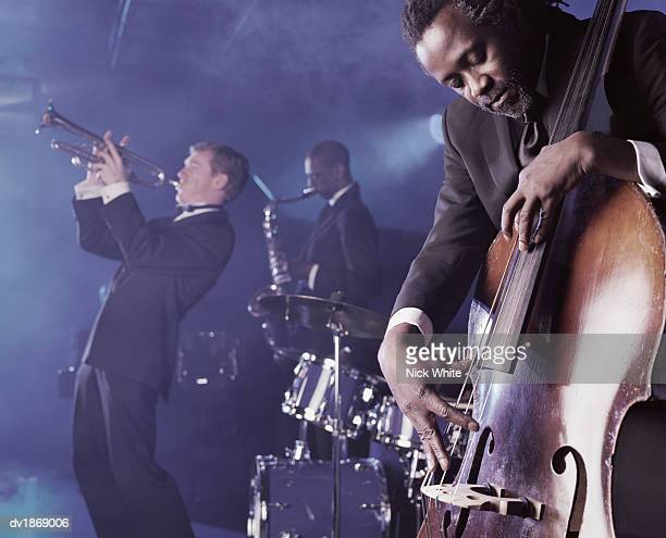 jazz band playing on stage in a nightclub, musician plucking a double bass - jazz stock pictures, royalty-free photos & images